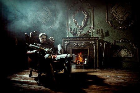 Noble knight in armor sits in armchair in a medieval castle. 写真素材