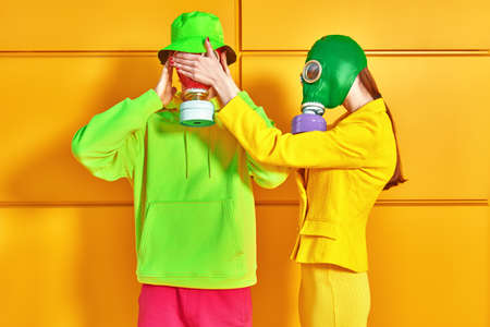 Stop environmental pollution. A couple of modern young people in bright clothes and gas masks posing by a yellow industrial wall.