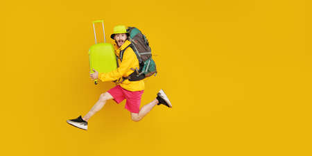 Full length portrait of emotional young hipster man jumping with backpack and suitcases. Tourism and travel, vacation. Studio portrait on a yellow background with copy space. 写真素材