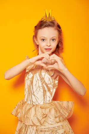 Dreams and kid's fashion. Portrait of a charming little princess girl in a golden dress and a crown showing a heart and smiling at camera. Yellow background.