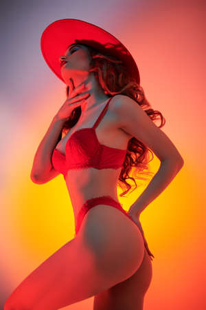 Underwear fashion. Portrait of an attractive young woman alluring in red sexy lingerie and a red hat. Studio shot in mixed colored light.