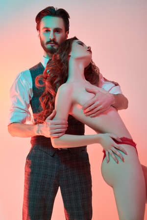 Handsome passionate man in elegant suit hugs sexy naked girl. Love and fashion.