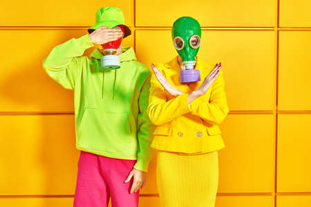 A couple of modern young people in bright clothes and gas masks posing by a yellow industrial wall. Stop environmental pollution. 免版税图像