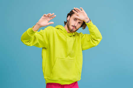People, emotions. Portrait of a handsome young man in a bright hoodie looking at the camera and covering himself with his hands. Studio portrait on a blue background. 免版税图像