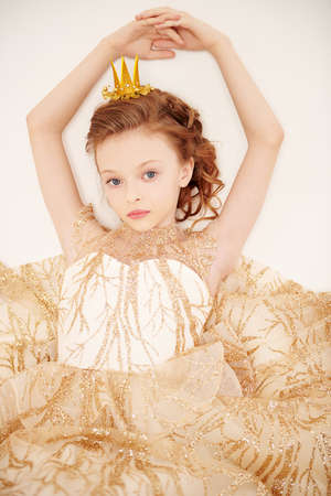Kid's fashion. Portrait of a beautiful little girl princess wearing evening dress and a crown. Studio portrait on a white background. 写真素材