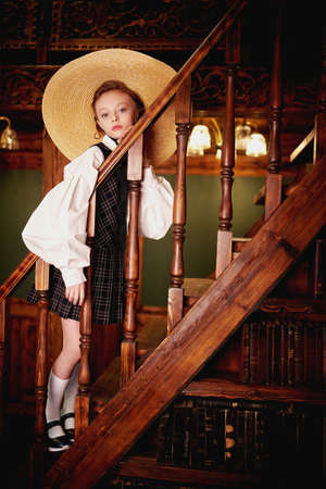 Full length portrait of a girl child in elegant classic school uniform and wide-brimmed hat posing in a luxurious vintage library interior. Kid's school fashion.