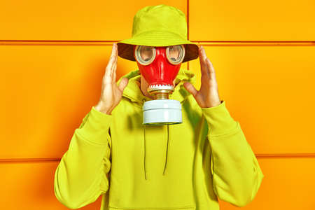 Technological disaster concept, air pollution. Portrait of a man in bright colored clothes and a red gas mask posing against a yellow industrial wall.