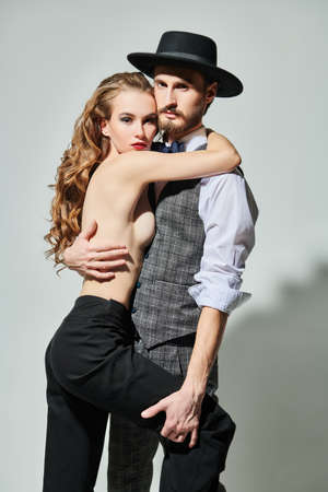 Love and fashion. Handsome passionate man in elegant suit embraces a beautiful girl with long curly hair. 写真素材