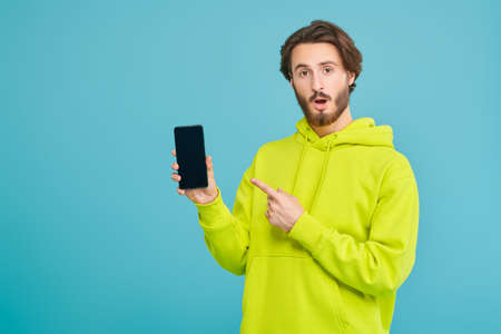 Portrait of a handsome young man holding his smartphone and is surprised. Studio portrait on a blue background with copy space.
