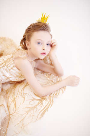 Charming little girl princess wearing evening dress and a crown. Kid's fashion. Studio portrait on a white background.