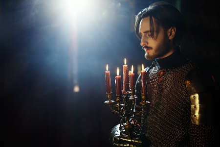 Tales of knights. A handsome medieval knight in armor stands with candles in the castle.