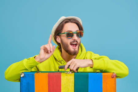 Vacation and travel concept. Emotional young man in a bright hoodie, sunglasses and a summer hat leaned on his bright colorful suitcase. Studio portrait on a blue background. 免版税图像