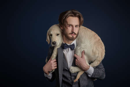 Fashion, man and dog. Portrait of a handsome man in elegant suit posing with a Golden Retriever puppy on a black background.