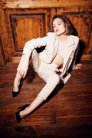 Full length portrait of an attractive young woman posing in classic white suit and high-heeled shoes in vintage interior.