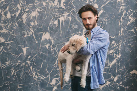 A man and a pet. Portrait of a young man hugging his Golden Retriever dog.