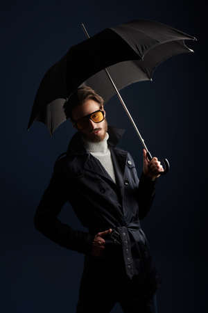 Portrait of a handsome fashion model man posing at studio in a raincoat and with an umbrella 写真素材