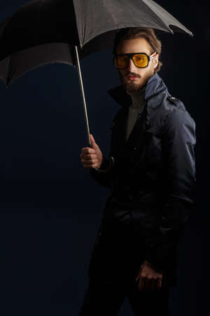 Men's fashion. Portrait of a handsome fashion model man posing at studio in a raincoat and with an umbrella