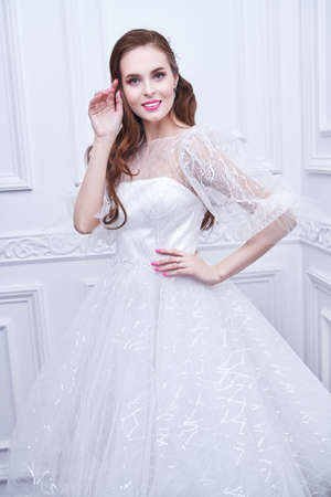 Wedding style. Portrait of a beautiful bride lady in a luxury white dress posing in classic white interior. Wedding make-up and hairstyle. 免版税图像