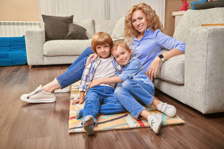 Happy family life at home. A mother spends time with her adorable children playing in a living room.