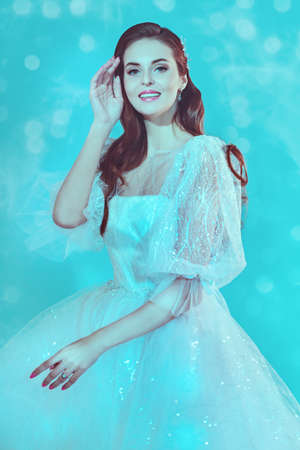 Portrait of a beautiful bride lady in a luxury white dress in soft blue light. Wedding make-up and hairstyle. Wedding fashion.