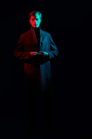 Full length portrait of a handsome young man standing in a coat in the dark, illuminated by red and green light. Men's fashion. 免版税图像