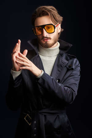 Portrait of a handsome fashion model man posing at studio in a raincoat and sunglasses
