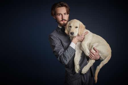 Men's fashion. Portrait of a handsome man in elegant suit holding his Golden Retriever dog on a black background. 免版税图像