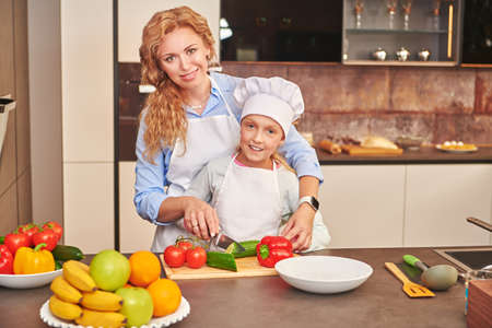 Adorable daughter and her mother cook dinner together, they cut a salad of fresh vegetables. Happy family. Healthy eating.