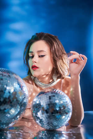 Glamorous young woman with evening make-up and hairstyle poses in jewelry with gems in the glow of disco balls.