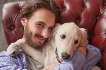 Handsome young man spends time with his pet Golden Retriever dog.