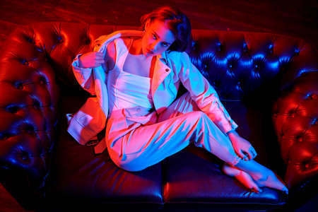 Attractive brunette woman sitting on a sofa in a dark room in mixed light.