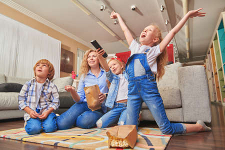 Happy family life at home. A mother spends time with her adorable children watching TV in a living room.