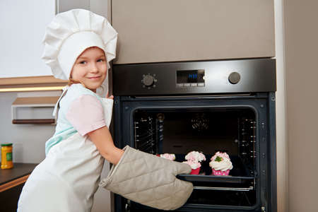 Happy little girl bakes cakes at home in the kitchen. Happy family. Healthy food at home, desserts.