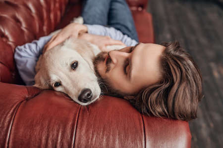 Happy calm young man lies on the couch and hugs his pet Golden Retriever dog. 写真素材