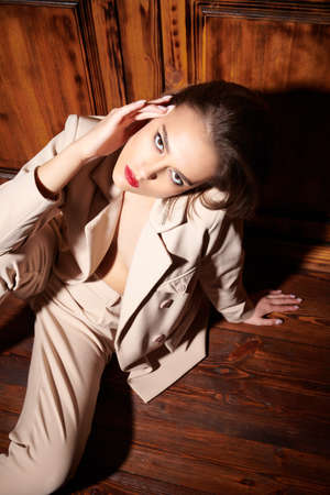 Young woman in classic white suit poses in a wooden interior. 写真素材