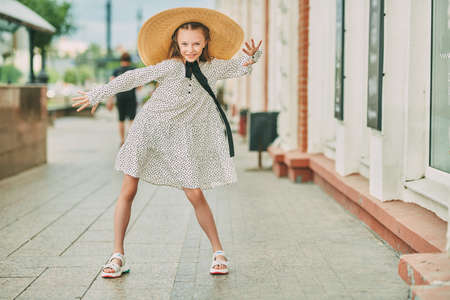 Beautiful emotional girl in elegant wide-brimmed straw hat and polka-dot dress poses on a city street. Kid's fashion.