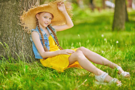 Happy summer holidays. Full length portrait of a lovely girl in straw hat having a rest in a summer park.