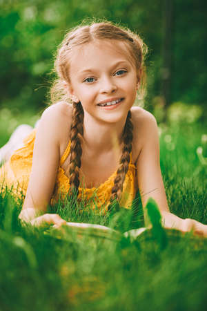 Smiling cute girl with pigtails lies on a green lawn with a book. Happy summer child. Walk in the park.