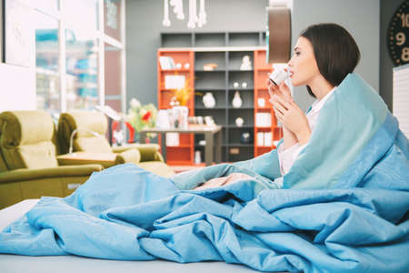 Happy people and lifestyle concept. Beautiful happy girl having a rest in her cozy bright living room. She sits, wrapped in a blanket and drinks coffee. 写真素材