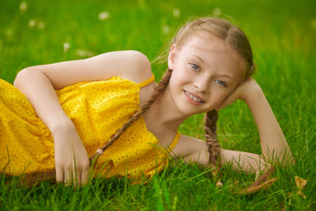 Happy summer child. Portrait of a cute girl with pigtails lying on a green lawn and smiling. Walk in the park.