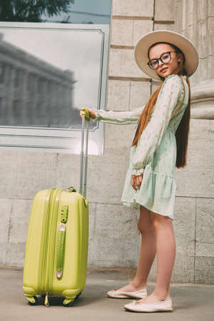 Modern child girl walks along the street of the city with a suitcase. Summer holiday, vacation and travel. 写真素材