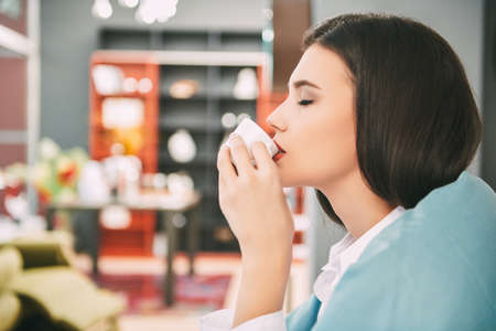 Happy young woman sits, wrapped in a blanket and drinks coffee. Beautiful happy girl having a rest in her cozy bright living room. Happy people and lifestyle concept.