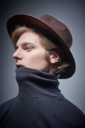 Artistic young man in a wide-brimmed hat and a turtleneck looks away. Studio portrait on a gray background. 写真素材