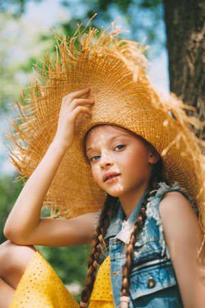 Portrait of a cute girl in straw hat walking in the park and smiling at camera. Happy summer holidays. 写真素材