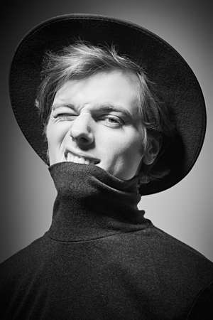 Art portrait of an artistic young man in a wide-brimmed hat and a turtleneck. Black-and-white studio portait.