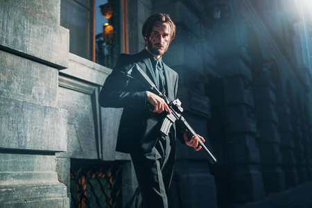 Wounded special agent with a rifle on a mission on the street of a night city. Underworld.
