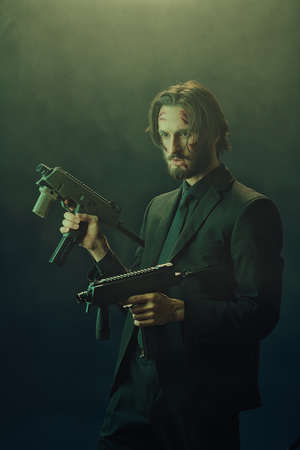 Brave special agent in a black suit with automatic guns in his hands on a dark foggy background.