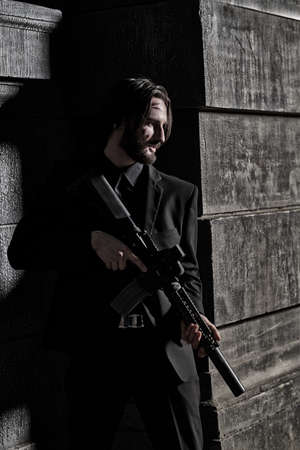 Underworld. Wounded special agent with automatic gun on a mission on the street of a night city.