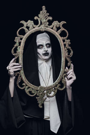 Halloween. Portrait of a scary devilish nun with a picture frame in her hands on a black background. Horrors.
