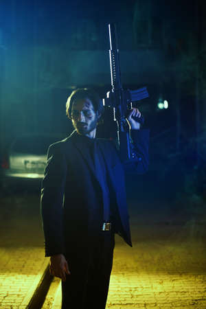 The criminal world in the big city. Courageous man with a rifle stands on a backstreet of a city at night. Special agent. Banque d'images
